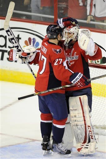 Washington Capitals goalie Braden Holtby, right, celebrates a 3-2 win over the Philadelphia Flyers with teammate Karl Alzner (27) after an NHL hockey game on Friday, Feb. 1, 2013, in Washington. (AP Photo/Nick Wass)
