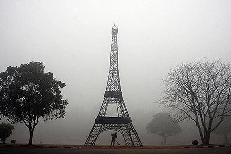 INDIA: A sweeper cleans the side of a road near a replica of the Eiffel Tower amid heavy fog in the early morning in the northern Indian city of Chandigarh January 18, 2010.