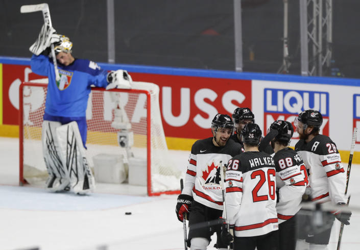 Italy's goaltender Davide Fadani, left, reacts as Canada players celebrate after Canada's Maxime Comtois scored his side's sixth goal during the Ice Hockey World Championship group B match between Italy and Canada at the Arena in Riga, Latvia, Sunday, May 30, 2021. (AP Photo/Sergei Grits)