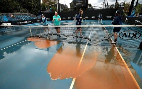 <span>Staff are seen attempting to clean dirt off the outside courts, caused by rainfall in the Melbourne area </span> <span>Credit: GETTY IMAGES </span>