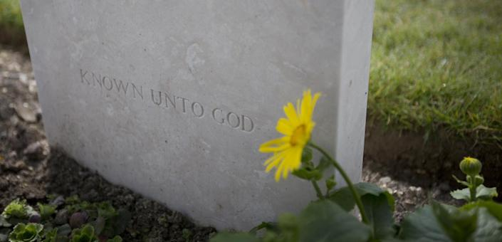 A flower grows next to the epitaph 'Known Unto God' on a gravestone for an unknown World War One soldier at Dud's Corner Cemetery in Loos-en-Gohelle, France on Thursday, March 13, 2014. Private William McAleer, of the 7th Battalion, Royal Scots Fusiliers, was killed in action on Sept. 26, 1915 during the Battle of Loos and his name has been on the wall of the missing at Dud's Corner for nearly 100 years. His body was found and identified in 2010, during routine construction in the area, and he will be reburied with full military honors, along with 19 unknown soldiers, at the Loos British Cemetery on Friday, March 14, 2014. (AP Photo/Virginia Mayo)