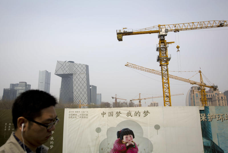 """FILE - In this Wednesday, April 2, 2014 file photo, a man walks past a Chinese government propaganda billboard with the words """"China dream, is my dream"""" near a construction site in Beijing. China's leaders have unveiled a mini-stimulus aimed at shoring up sputtering growth in the world's No. 2 economy. Under the measures announced by Premier Li Keqiang on Wednesday, small businesses will get bigger tax breaks, social housing will be built to replace shantytowns and railway construction will be sped up. (AP Photo/Andy Wong, File)"""