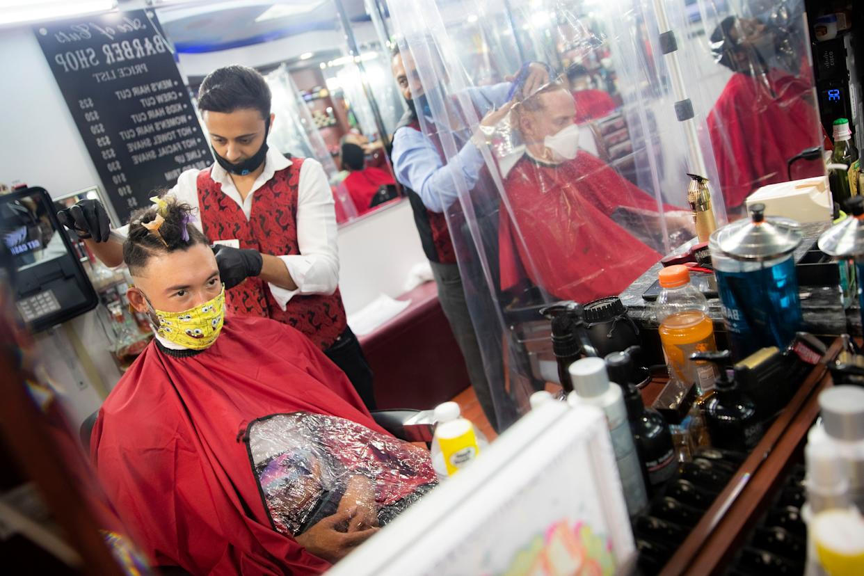 Brian Nieh wears a protective mask as he receives a haircut at Ace of Cuts barbershop, on Monday, June 22, 2020, in the Manhattan borough of New York.