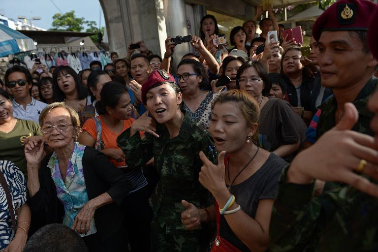Soldiers dance with residents at a military event organised to 'return happiness to the people' at Victory Monument, the site of recent anti-coup rallies in Bangkok, on June 4, 2014