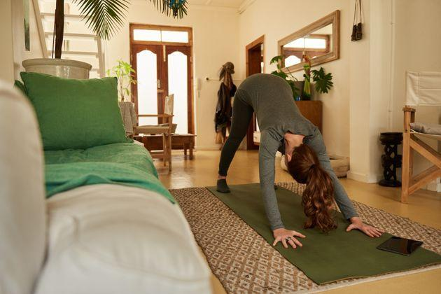 Start your a.m. with a downward dog to get your blood flowing and increase alertness. (Photo: Mavocado via Getty Images)