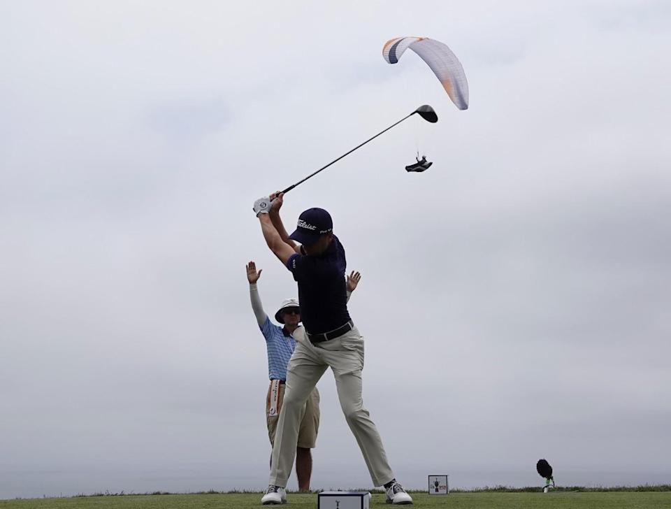 A paraglider flies near the fourth hole as Justin Thomas tees off during the second round.