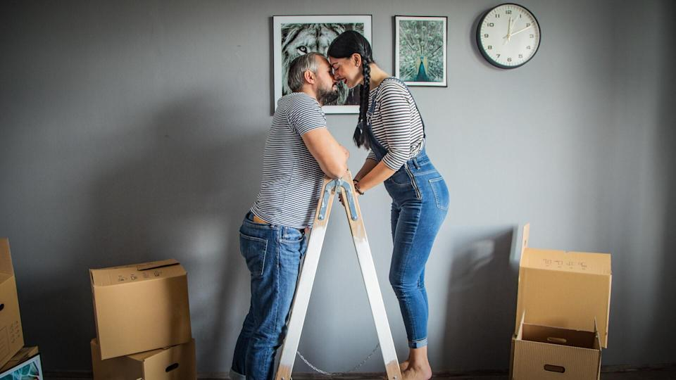 young family of new homebuyers putting up picture frames