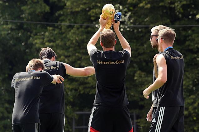 Germany defender Philipp Lahm (L) dances with teammates Mats Hummels (2ndL) as Thomas Mueller (C) celebrates with the trophy during a World Cup victory parade of Germany's football national team on July 15, 2014 at Berlin's Brandenburg Gate (AFP Photo/Adam Berry)