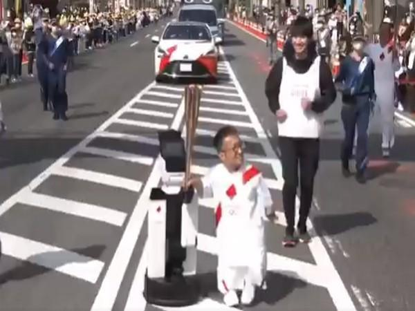 A robot helping to carry the Olympic torch (Image: #Tokyo 2020's Twitter)