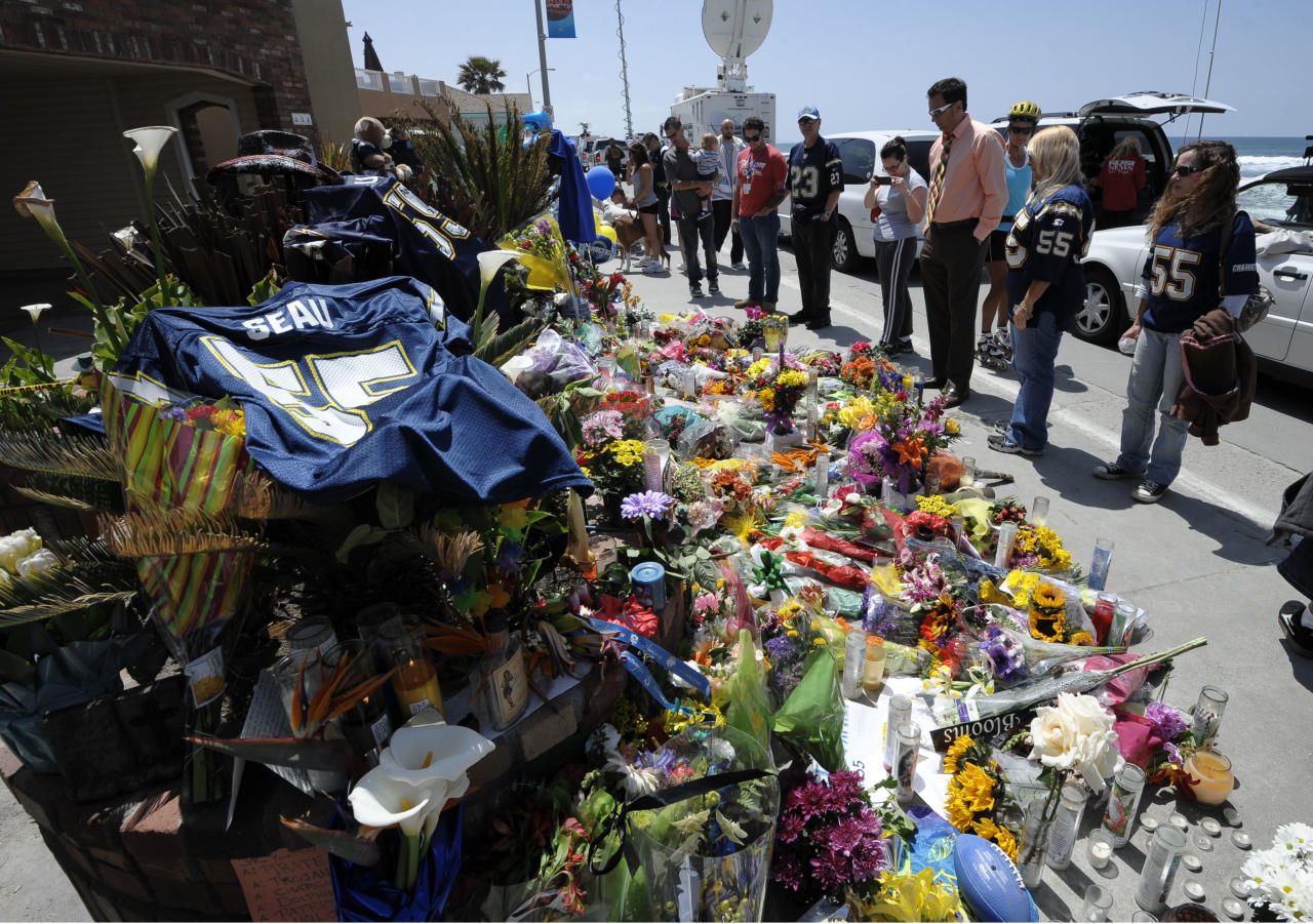 A San Diego Chargers #55 jersey sits in the foreground as fans look over a memorial in driveway of former NFL star Junior Seau's house, Thursday, May 3, 2012, in Oceanside, Calif. Seau's death in Oceanside, in northern San Diego County, stunned the region he represented with almost reckless abandon. (AP Photo/Denis Poroy)
