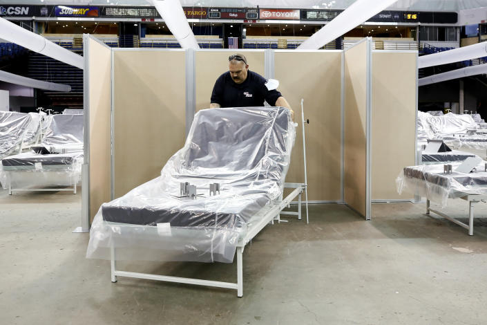 FILE— In this April 18, 2020 file photo Robert Reynolds, of the California Department of Forestry and Fire Protection, moves a bed into position as work is performed to turn Sleep Train Arena into a 400-bed emergency field hospital to help deal with the coronavirus outbreak, in Sacramento, Calif. The state has reopened the arena, which had handled only nine patients over 10 weeks, and other facilities to help handle a new surge of coronavirus patients, but is using little more than a handful of volunteers from Gov. Gavin Newsom's California Health Corps who originally helped staff the facility. (AP Photo/Rich Pedroncelli, File)