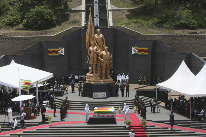 """Pallbearers stand next to the coffins of government ministers who died of COVID-19, at the Heroes Acre in Harare, Thursday, Jan. 21, 2021. Zimbabwean President Emmerson Mnangagwa who presided over the burial called the pandemic """"evil"""" and urged people to wear masks, practice social distancing and sanitize, as cases across the country increased amid a fragile health system. (AP Photo/Tsvangirayi Mukwazhi)"""