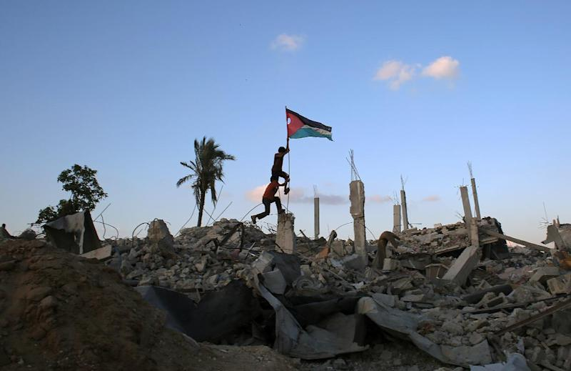 Children in Khan Yunis' Khuzaa neighbourhood in the southern Gaza Strip place a Palestinian flag on October 1, 2014, in the rubble of a building destroyed during the Israeli army's summer offensive on the Gaza Strip (AFP Photo/Said Khatib)