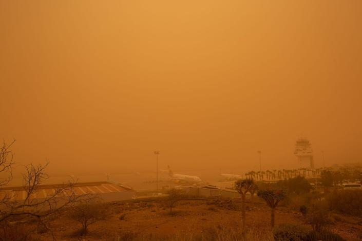 Planes are pictured at Tenerife SouthReina Sofia Airport during a sandstorm on February 23, 2020 on the Canary Island of Tenerife.