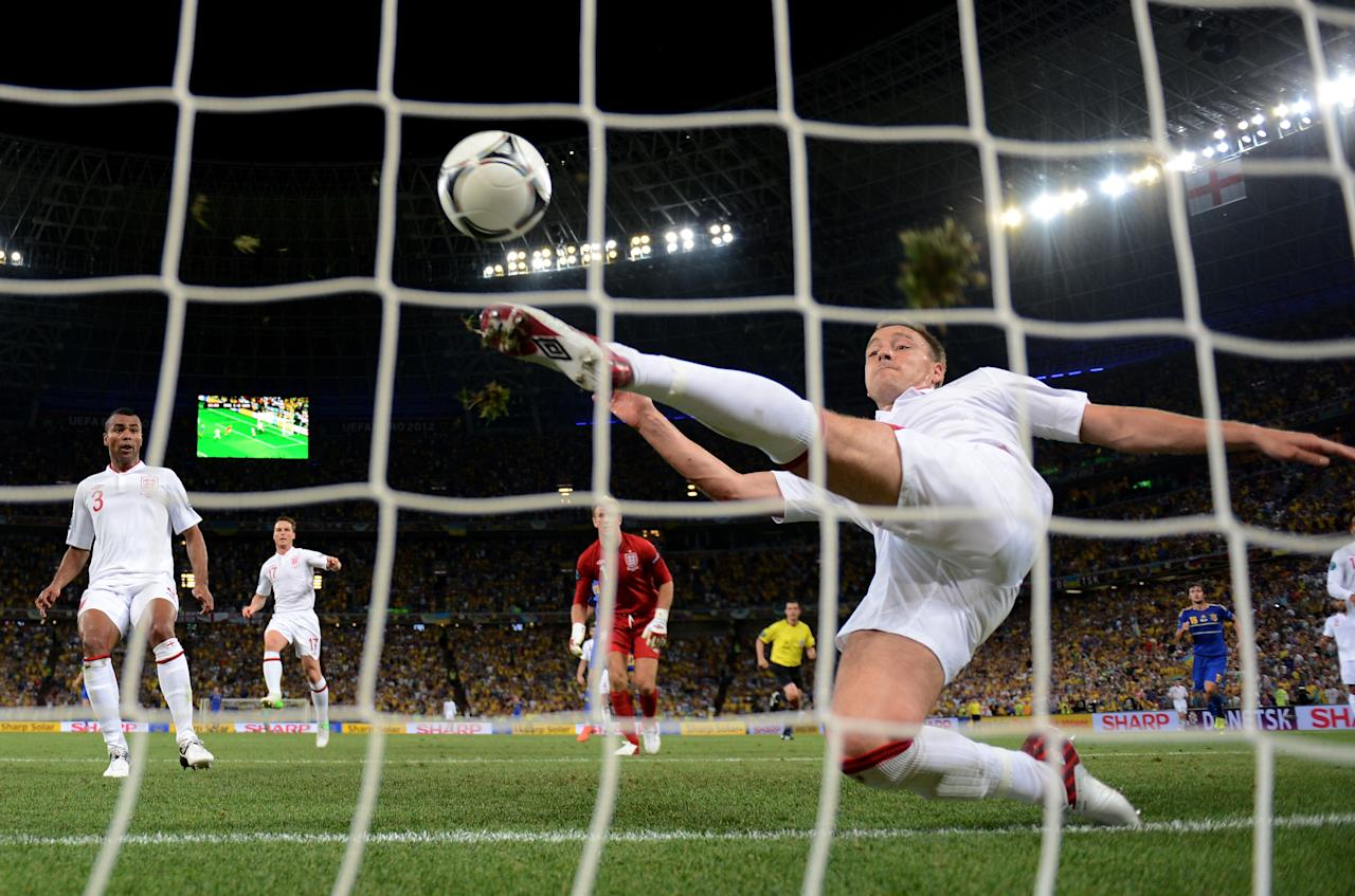DONETSK, UKRAINE - JUNE 19:  John Terry of England clears an effort from  Marko Devic of Ukraine off the line during the UEFA EURO 2012 group D match between England and Ukraine at Donbass Arena on June 19, 2012 in Donetsk, Ukraine.  (Photo by Laurence Griffiths/Getty Images)