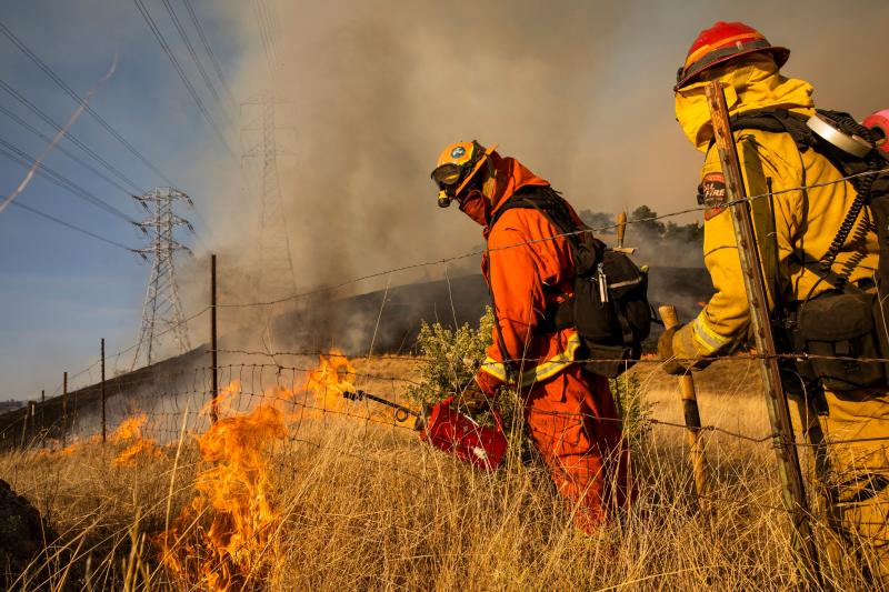 Firefighters set a back fire along a hillside near PG&E power lines during firefighting operations to battle the Kincade Fire in Healdsburg, California on October 26, 2019. - US officials on October 26 ordered about 50,000 people to evacuate parts of the San Francisco Bay area in California as hot dry winds are forecast to fan raging wildfires. (Photo by Philip Pacheco / AFP) / The erroneous source appearing in the metadata of this photo by Philip Pacheco has been modified in AFP systems in the following manner: [AFP] instead of [www.philippachecophoto.com]. Please immediately remove the erroneous mention from all your online services and delete it from your servers. If you have been authorized by AFP to distribute it to third parties, please ensure that the same actions are carried out by them. Failure to promptly comply with these instructions will entail liability on your part for any continued or post notification usage. Therefore we thank you very much for all your attention and prompt action. We are sorry for the inconvenience this notification may cause and remain at your disposal for any further information you may require. (Photo by PHILIP PACHECO/AFP via Getty Images)