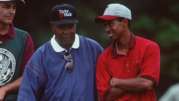 Earl Woods stands next to a smiling Tiger Woods on a golf course.