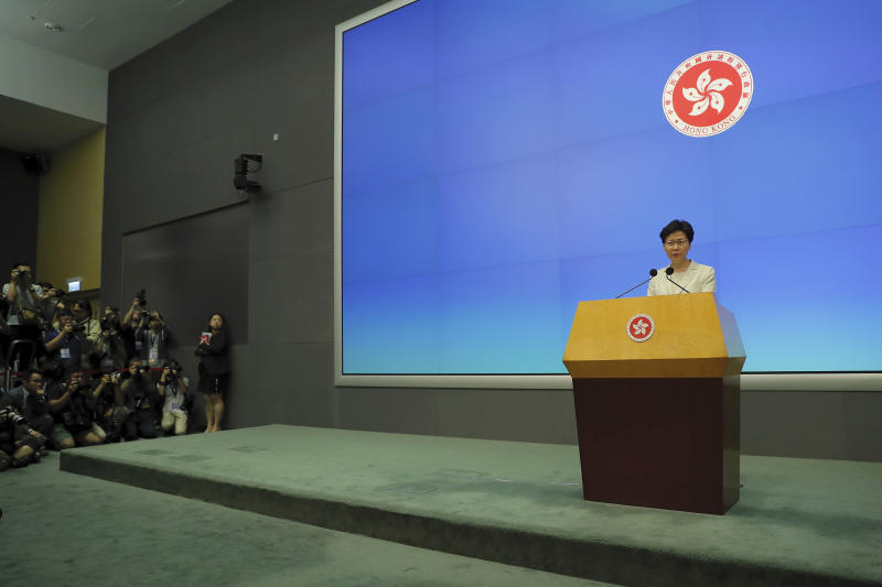 Photographers aim at Hong Kong Chief Executive Carrie Lam speak on stage during a press conference at the Legislative Council in Hong Kong, Tuesday, June 18, 2019. Lam apologized Tuesday for an unpopular extradition bill that drew massive protests and indicated that it will not be revived during the current legislative session. (AP Photo/Kin Cheung)