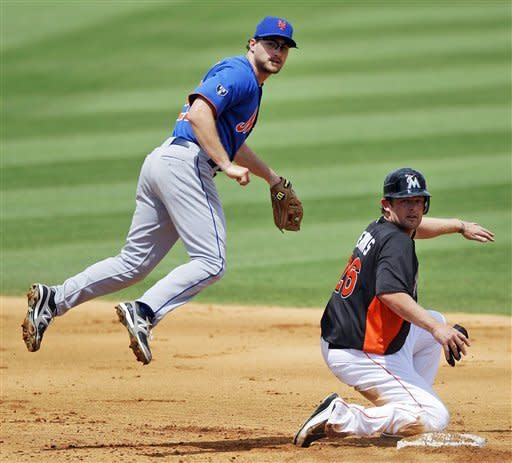 New York Mets second baseman Daniel Murphy, left, and Miami Marlins' Austin Kearns look to first base after Murphy forced out Kearns while trying to make a double play in the fourth inning of a spring training baseball game in Jupiter, Fla., Saturday, March 31, 2012. Miami won 6-5. (AP Photo/Patrick Semansky)