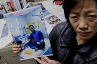 Allison Lee of the Ilan Migrant Fishermen Union holds a picture of missing Indonesian fisherman Tolani