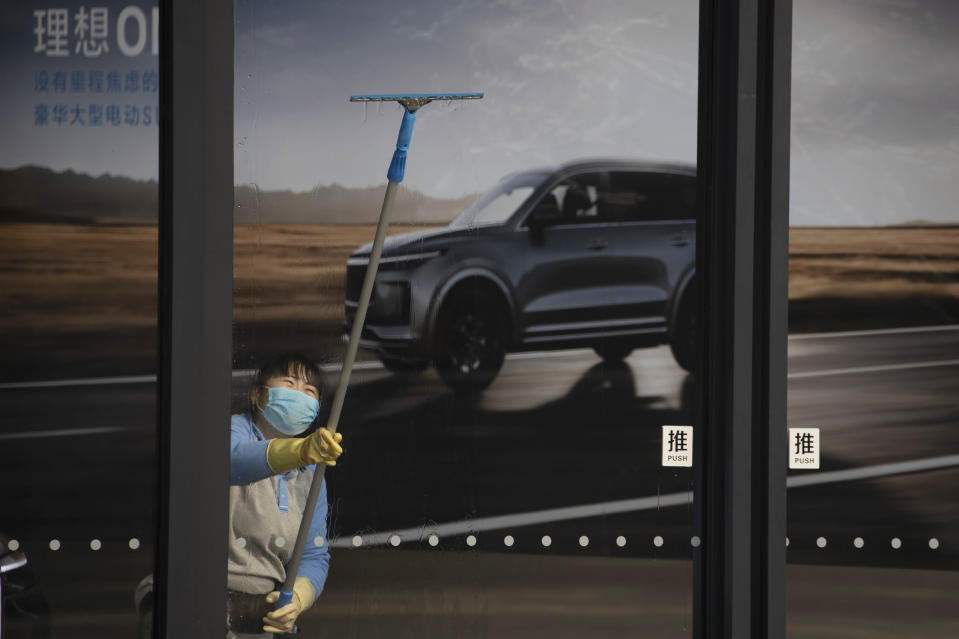 In this photo taken Wednesday, Feb. 12, 2020, a worker cleans the glass doors at an empty auto showroom in Beijing, China. Millions of Chinese workers and entrepreneurs are bearing the rising costs of an anti-virus campaign that has shut down large sections of the economy. The government has imposed restrictions nationwide that have stalled travel and sales of real estate and autos. (AP Photo/Ng Han Guan)