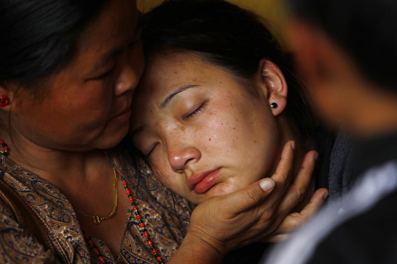 Daughter of Nepalese mountaineer Ang Kaji Sherpa, killed in an avalanche on Mount Everest, cries as her father's body is brought to the Sherpa Monastery in Katmandu, Nepal, Saturday, April 19, 2014. Rescuers were searching through piles of snow and ice on the slopes of Mount Everest on Saturday for four Sherpa guides who were buried by an avalanche that killed 12 other Nepalese guides in the deadliest disaster on the world's highest peak. The Sherpa people are one of the main ethnic groups in Nepal's alpine region, and many make their living as climbing guides on Everest and other Himalayan peaks. (AP Photo/Niranjan Shrestha)