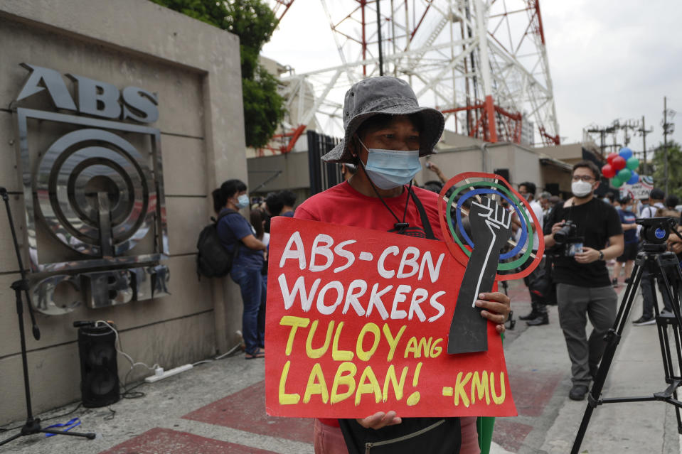 """A supporter holds a slogan that reads: """"ABS-CBN workers, Fight continues"""" during a rally outside the ABS-CBN headquarters in Quezon City, Philippines, Friday July 10, 2020. Philippine lawmakers voted Friday to reject the license renewal of the country's largest TV network, shutting down a major news provider that had been repeatedly threatened by the president over its critical coverage. (AP Photo/Aaron Favila)"""