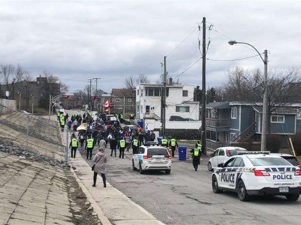 An anti-mask protest makes its way through the streets of Hull in Gatineau, Que., on March 27, 2021.