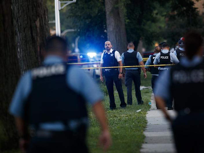 An officer investigates the scene of a deadly shooting where a 7-year-old girl and a man was fatally shot in Chicago on Sunday: (Chicago Tribune)