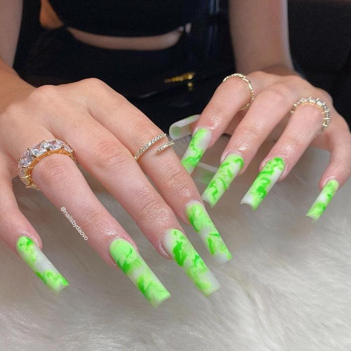 Cloudy swirls of shamrock and slime greens run through these white, square nails. Vo expertly sculpted these square nails into a long shape, which really elevates the marbled neon-green manicure.