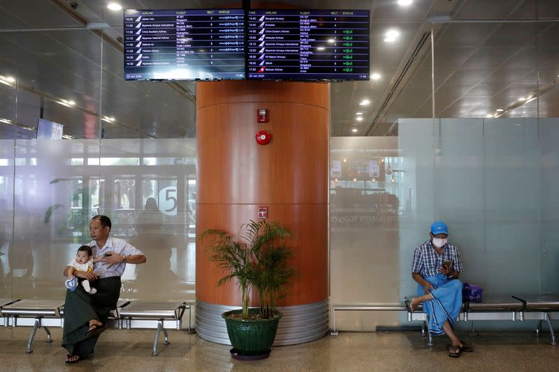 People wear face masks at the arrival hall of Yangon international airport in Yangon