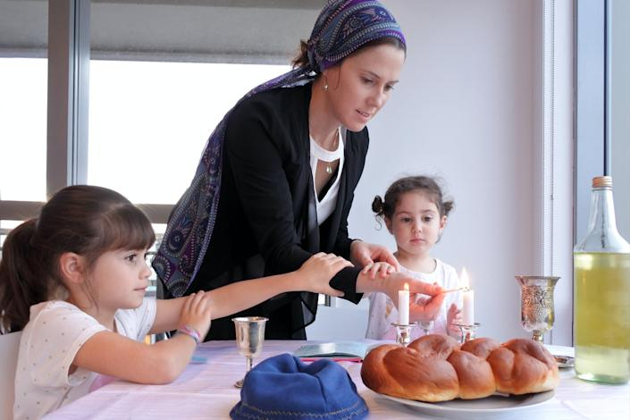 """<span class=""""caption"""">Jewish mother lighting candles on Sabbath eve.</span> <span class=""""attribution""""><a class=""""link rapid-noclick-resp"""" href=""""https://www.gettyimages.com/detail/photo/jewish-mother-and-daughters-light-sabbath-candles-royalty-free-image/824781364?adppopup=true"""" rel=""""nofollow noopener"""" target=""""_blank"""" data-ylk=""""slk:Rafael Ben-Ari/Photodisc Archive via Getty Images Images"""">Rafael Ben-Ari/Photodisc Archive via Getty Images Images</a></span>"""