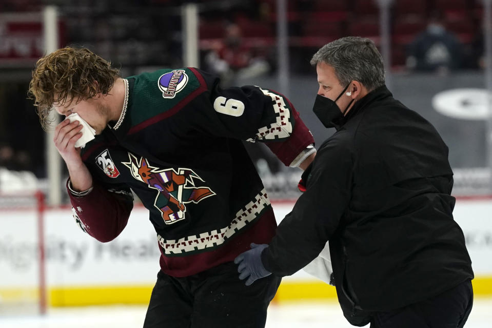 Arizona Coyotes defenseman Jakob Chychrun (6) gets helped off the ice by Head Athletic Trainer Dave Zenobi after getting hit with a high stick in the second period during an NHL hockey game against the Colorado Avalanche, Tuesday, March 23, 2021, in Glendale, Ariz. Chychrun returned to the game. (AP Photo/Rick Scuteri)