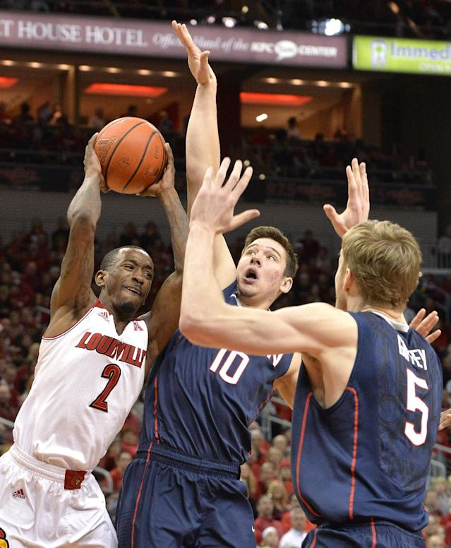 Louisville's Russ Smith, left, passes the ball away from the pressure of Connecticut's Tyler Olander, center, and Niels Giffey during the second half of an NCAA college basketball game, Saturday, March 8, 2014, in Louisville, Ky. Louisville defeated UConn 81-48. (AP Photo/Timothy D. Easley)