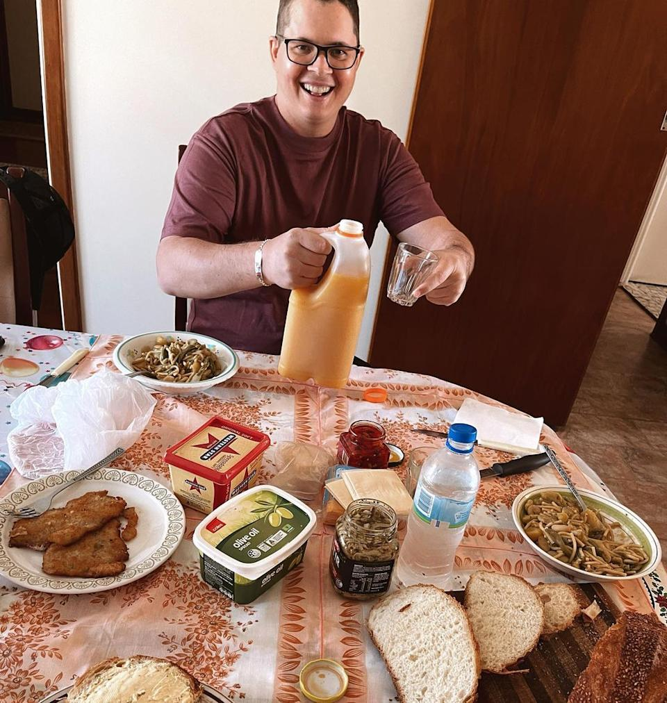 Former Home & Away star Johnny Ruffo smiles while sitting at a dining table full of food