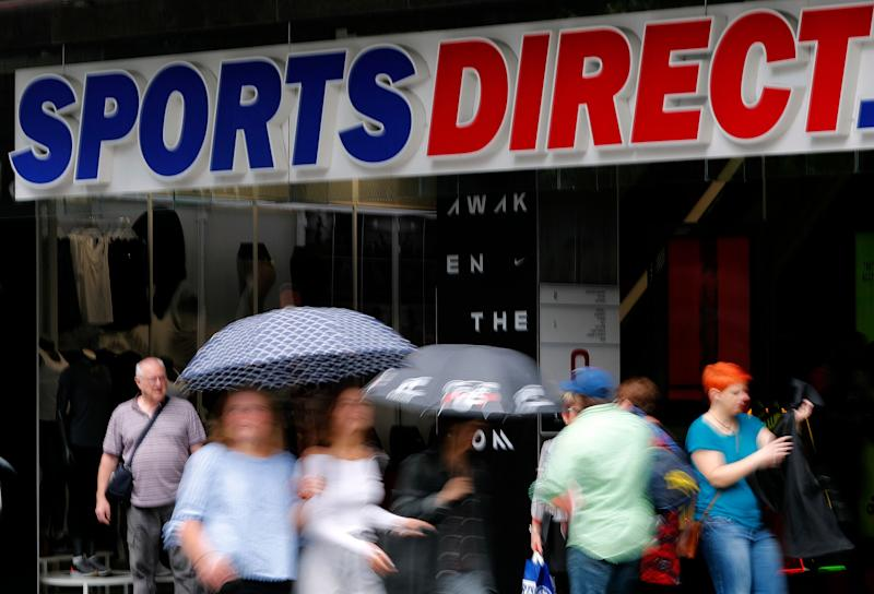 Pedestrians walk past British retailer Sports Direct store at Oxford Street in London, Friday, Aug. 10, 2018. British retailer Sports Direct said Friday that it has bought struggling department store chain House of Fraser, just hours after the 169-year-old business went into administration. (AP Photo/Frank Augstein)