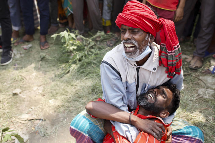 Relatives cry as rescuers recover bodies after a ferry sank Sunday night after being hit by a cargo vessel in the Shitalakkhya River in Narayanganj district, outside Dhaka, Bangladesh, Monday, April 5, 2021. (AP Photo/Mushfiqul Alam)