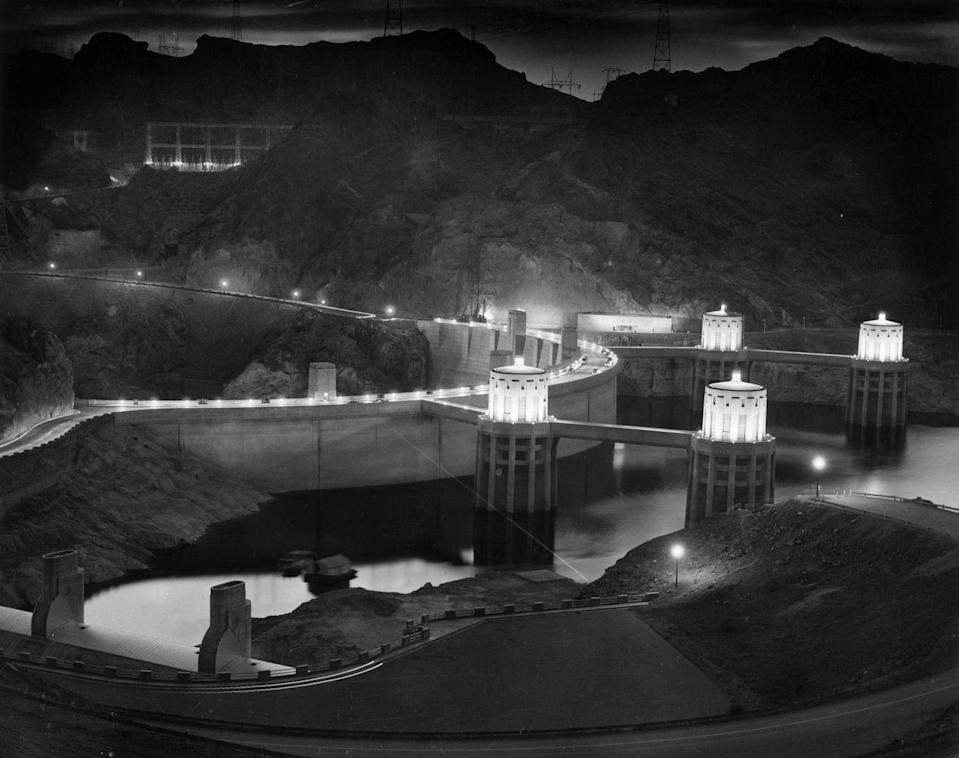 """<p>Built between 1931 and 1935, the Art Deco-detailed dam was the most expensive engineering project in the U.S. at the time and became the tallest dam in the country at <a href=""""https://www.roadsbridges.com/engineering-behind-hoover-dam-and-its-bypass"""" rel=""""nofollow noopener"""" target=""""_blank"""" data-ylk=""""slk:726 feet tall"""" class=""""link rapid-noclick-resp"""">726 feet tall</a>. Today, it's still the <a href=""""https://www.usbr.gov/lc/hooverdam/history/essays/biggest.html"""" rel=""""nofollow noopener"""" target=""""_blank"""" data-ylk=""""slk:second-tallest dam"""" class=""""link rapid-noclick-resp"""">second-tallest dam</a> and the tallest concrete dam. It required <a href=""""https://www.popularmechanics.com/technology/infrastructure/g2837/7-most-serious-dams-us/"""" rel=""""nofollow noopener"""" target=""""_blank"""" data-ylk=""""slk:91.8 billion cubic feet of concrete"""" class=""""link rapid-noclick-resp"""">91.8 billion cubic feet of concrete</a> to create the arch-gravity dam with a 600-foot-wide base, weighing 6.6 million tons in total.</p>"""