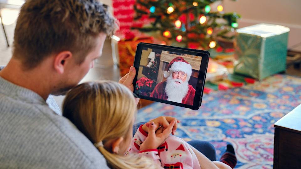 A father and daughter, talking to Santa Claus on a computer video conference call.