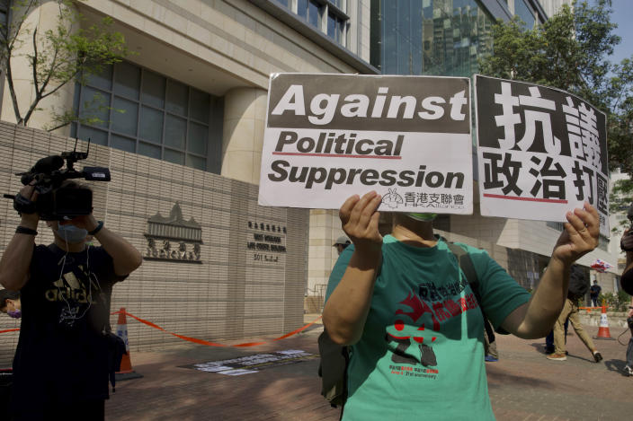 A pro-democracy supporter raises placards outside a court in Hong Kong Thursday, April 1, 2021. Seven pro-democracy advocates were convicted Thursday for organizing and participating in an unlawful assembly during massive anti-government protests in 2019, as Hong Kong continues its crackdown on dissent. (AP Photo/Vincent Yu)
