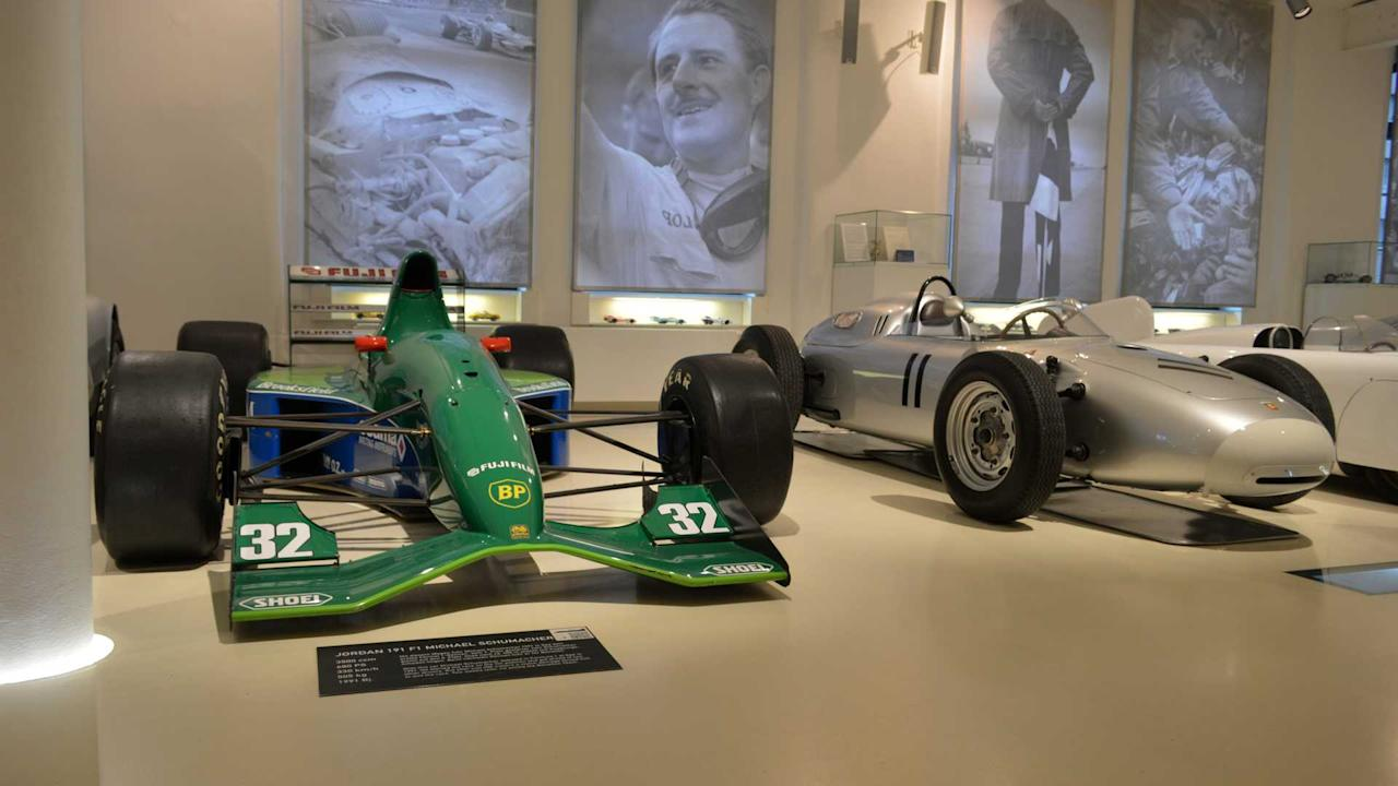 """<p>Two of several racing cars on display at Prototyp.</p> <p>On the left is one of seven Ford-powered Jordan 191s and on the right is one of five Porsche 718/2-02 Formula 2 cars.</p> <p>The Jordan is perhaps best-known as the car that gave the great Michael Schumacher his Formula 1 debut. The German driver qualified an impressive seventh in the 1991 Belgian Grand Prix and although mechanical gremlins limited his debut to just a few metres.</p> <p>While Porsche is perhaps better known for its sports car exploits, in the 1950s and 1960s the German manufacturer was a fixture in the single seater arena.</p> <p>It made its debut at the 1959 Monaco Grand Prix, and when F1 adopted F2 regulations a couple of years later, thePorsche 718/2-02 became a fixture in the world championship.</p><h2>More motoring museums</h2><ul><li><a href=""""https://uk.motor1.com/news/251681/mercedes-museum-stuttgart-merc-paradise/?utm_campaign=yahoo-feed"""">The Mercedes Museum in Stuttgart is a Merc lovers paradise</a></li><br><li><a href=""""https://uk.motor1.com/features/237276/car-museum-plans-cotswolds/?utm_campaign=yahoo-feed"""">A world-leading car museum is being planned for the Cotswolds</a></li><br></ul>"""