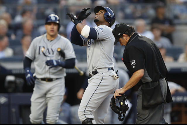 Tampa Bay Rays on-deck batter Avisail Garcia, left, watches as Yandy Diaz steps on the plate after hitting a solo home run during the fourth inning of a baseball game against the New York Yankees, Tuesday, July 16, 2019, in New York. Home plate umpire Gerry Davis is at right. (AP Photo/Kathy Willens)