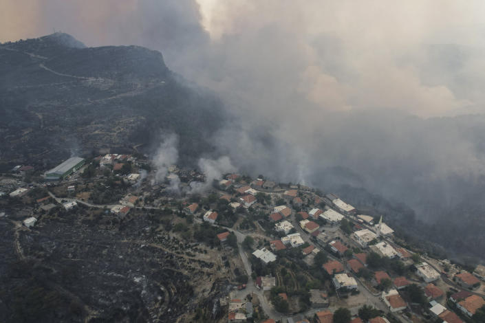 An aerial view of burning Sirtkoy village, near Manavgat, Antalya, Turkey, Sunday, Aug. 1, 2021. More than 100 wildfires have been brought under control in Turkey, according to officials. The forestry minister tweeted that five fires are continuing in the tourist destinations of Antalya and Mugla. (AP Photo)