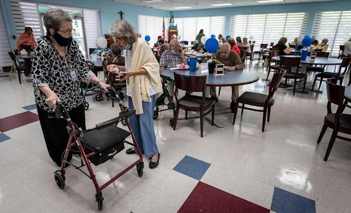 From left, Gregoria Reyes, 100, talks to Esther Ayllon, 88, in the dining room at Carroll Manor Senior Center in Miami on May 25, 2021. This is the first week of some senior centers reopening their cafeterias.