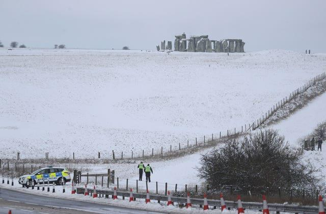 Police at a snowy Stonehenge in Wiltshire