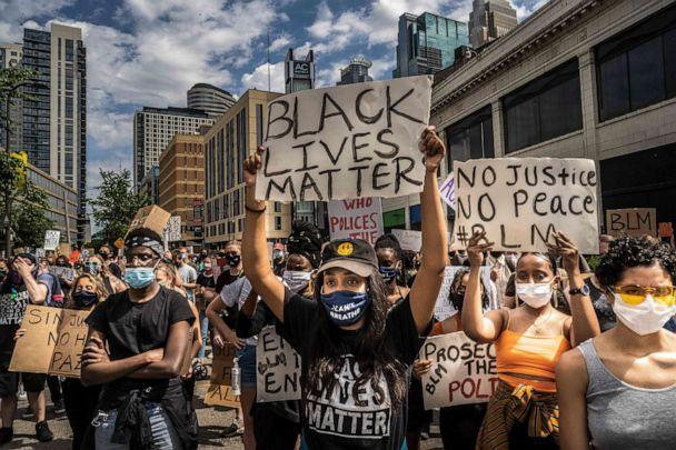 PHOTO: Protesters hold signs outside the Minneapolis 1st Police precinct during a demonstration against police brutality and racism on June 13, 2020 in Minneapolis, Minnesota. (Kerem Yucel/AFP via Getty Images)