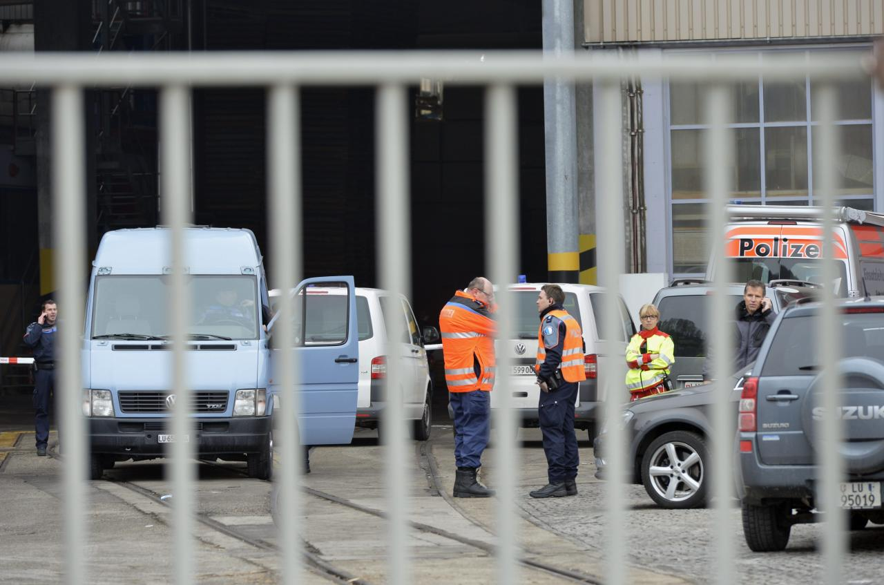 """Police stand in front of a wood-processing company in Menznau, central Switzerland, Wednesday, Feb. 27, 2013, where several people were killed in a shooting. Police in Lucerne canton (state) said in a statement that the shooting occurred shortly after 9 a.m. at the premises of Kronospan, a company in the small town west of Lucerne. They said there were """"several dead and several seriously injured people"""" and that rescue services were deployed and the scene sealed off. (AP Photo/Keystone, Urs Flueeler)"""
