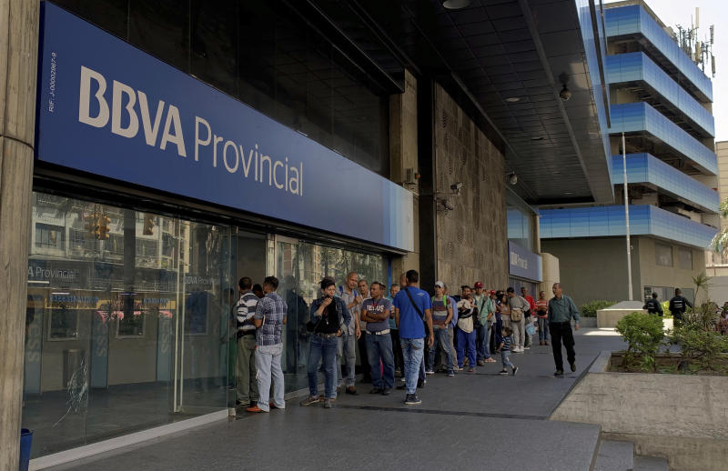 Customer line up outside a branch of Banco Provincial bank in Caracas, Venezuela, Monday, May 13, 2019. After 16 years of currency controls, the government is allowing its Bolivar to be exchanged on the floating market starting Monday, starting at 5,200 Bolivars per U.S. dollar. (AP Photo/Fernando Llano)