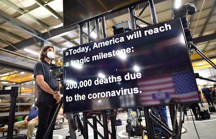 Joe Biden's teleprompter refers to the U.S. coronavirus death toll as he speaks at a campaign event Monday. (Mark Makela/Reuters)