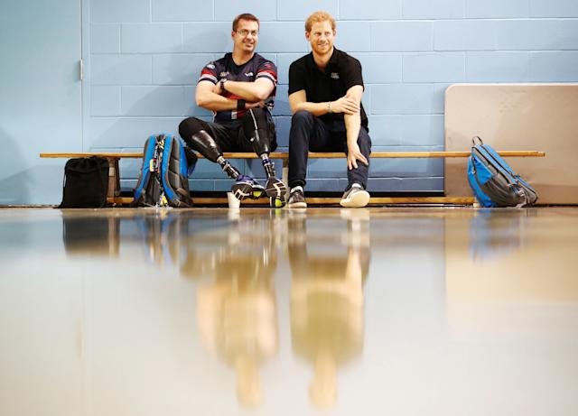 Prince Harry sits with one of theathletes at the Toronto Pan Am Sports Centre.